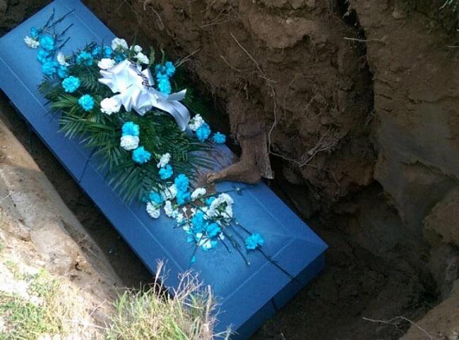 Gamba in decomposizione esce dal terreno e si poggia sulla bara: scena horror al funerale