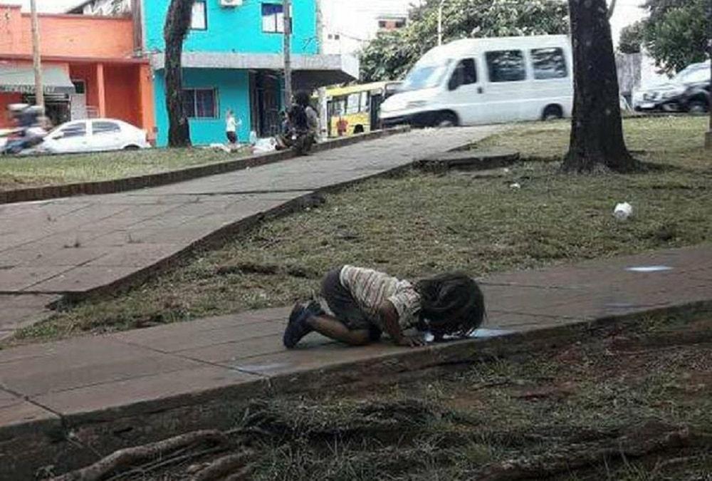 Bambino beve dalla pozzanghera, la foto simbolo della