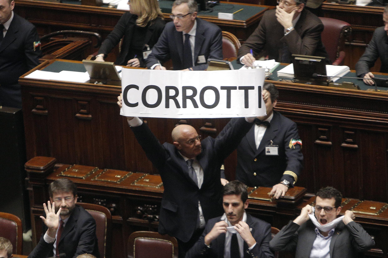 Fabio Rampelli di Fratelli d'Italia mostra uno striscione durante la bagarre alla Camera scatenata dal M5S dopo il voto