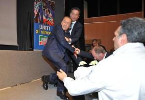 """Berlusconi inciampa sul palco: """"Colpa della sinistra"""" (foto Ansa)"""