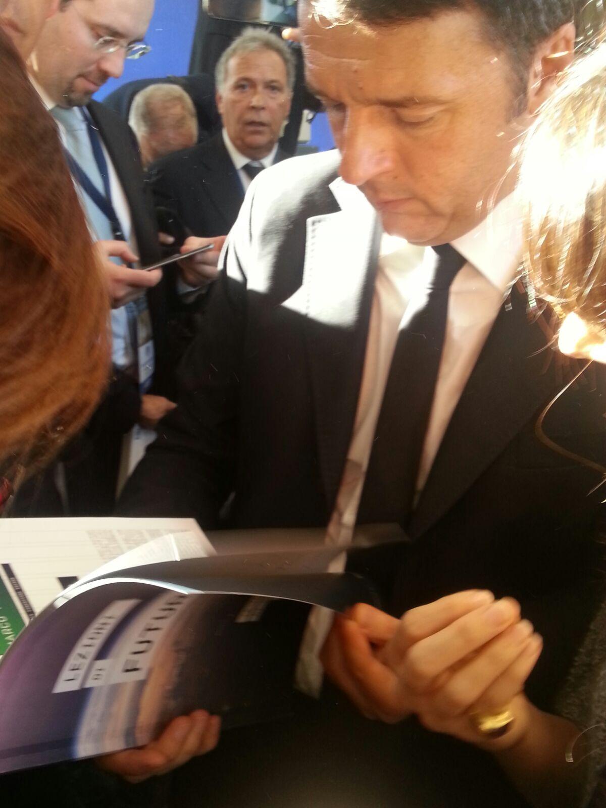 """Il presidente del consiglio Matteo Renzi sfoglia """"Lezioni di Futuro"""" charter sull'innovazione che Edison ha prodotto durante i mesi di EXPO"""