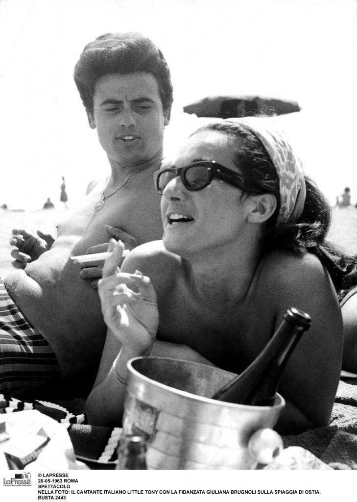 © LAPRESSE20-05-1963 ROMASPETTACOLONELLA FOTO: IL CANTANTE ITALIANO LITTLE TONY CON LA FIDANZATA GIULIANA BRUGNOLI SULLA SPIAGGIA DI OSTIA.BUSTA 2443