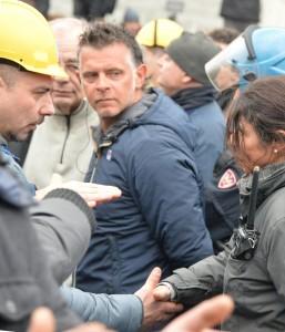 Guarda la versione ingrandita di Una funzionaria di polizia, dopo essersi tolta il casco, stringe la mano a un lavoratore, come segno di distensione tra manifestanti e polizia alla manifestazione dei lavoratori Ilva a Genova, 27 gennaio 2016. Davanti a questo gesto i lavoratori, che erano arrivati faccia a faccia con gli agenti in tenuta antisommossa, hanno fatto un passo indietro. E' il terzo giorno di proteste a Genova per i lavoratori dello stabilimento Ilva di Cornigliano iscritti alla Fiom che manifestano a difesa dell'Accordo di Programma firmato nel 2005 che a fronte della chiusura della lavorazione a caldo prevedeva il mantenimento dei livelli occupazionali e di reddito. ANSA / LUCA ZENNARO
