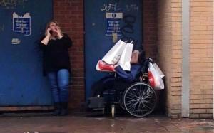 Badante usa disabile in sedia a rotelle come portaborse FOTO