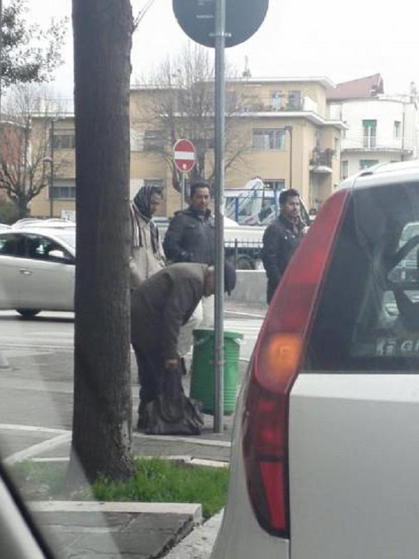 Pensionato rovista tra rifiuti: alle sue spalle migranti...