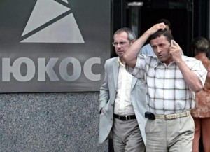 Guarda la versione ingrandita di epa04333691 (FILE) A file picture dated 02 August 2004 shows people walking past the Yukos logo at the entrance to the headquarters building in Moscow, Russia. According to news reports on 28 July 2014, Russia lost an ongoing legal case to the former shareholders of oil company Yukos, forcing the government to pay a record 50 billion dollars in compensation. The decision was passed down by the Permanent Court of Arbitration in The Hague, ending a lawsuit that began in 2005. The court ruled unanimously that the dissolution of Yukos, once the largest oil company in Russia, was politically motivated. Yukos was dissolved by the Russian government in 2003 after its chief executive, Mikhail Khodorkovsky, was found guilty of tax evasion. He served nine years in prison.  EPA/YURI KOCHETKOV