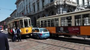 YOUTUBE Milano auto polizia incastrata tra tram piazza Scala