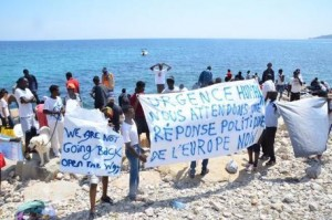 Guarda la versione ingrandita di Migrants hold signs as they stage a demonstration on the rocks off the coast of Ventimiglia, at the border between Italy and France, 14 June 2015. Migrants spent the night near the sea at the French-Italian border, after being refused entry into France. ANSA/ CARLO ALESSI