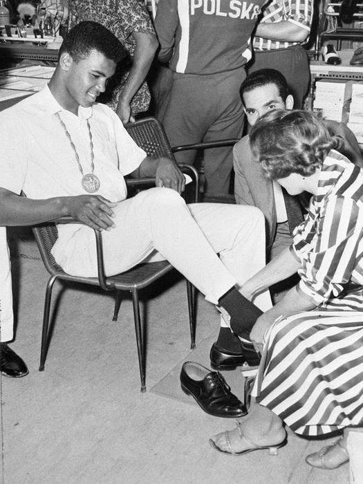 Il pugile Cassius Clay in un negozio della capitale a comprare delle scarpe. Porta al collo la medaglia d'oro vinta nella categoria dei medio-massimi.  Archivio Storico ANSA