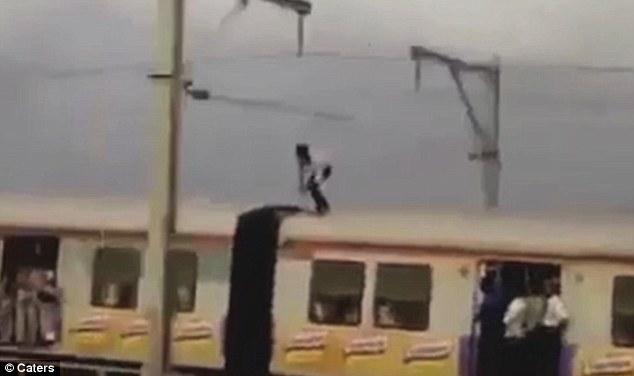In piedi sul treno in corsa, si abbassa per evitare i tralicci