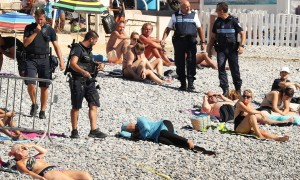 Guarda la versione ingrandita di Nizza, dorme col burqini in spiaggia: polizia glielo fa togliere e la multa