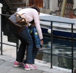 Guarda la versione ingrandita di Venezia, guerra ai barbari turisti: città latrina ma la colpa di chi è? Nella foto, mamma fa fare la pipi nel canale al suo bambino (dalla Nuova Venezia)
