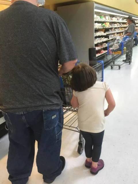 Lega capelli figlia al carrello e la trascina per il supermercato 01