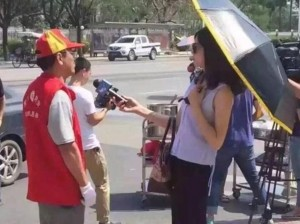 Guarda la versione ingrandita di Cina, reporter sui luoghi del tifone con ombrello e occhiali da sole