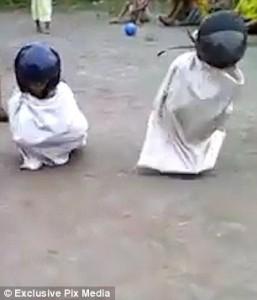 Corsa nei sacchi è estrema bambini indossano casco da motociclista e cadono a terra6