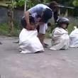 Corsa nei sacchi è estrema bambini indossano casco da motociclista e cadono a terra5