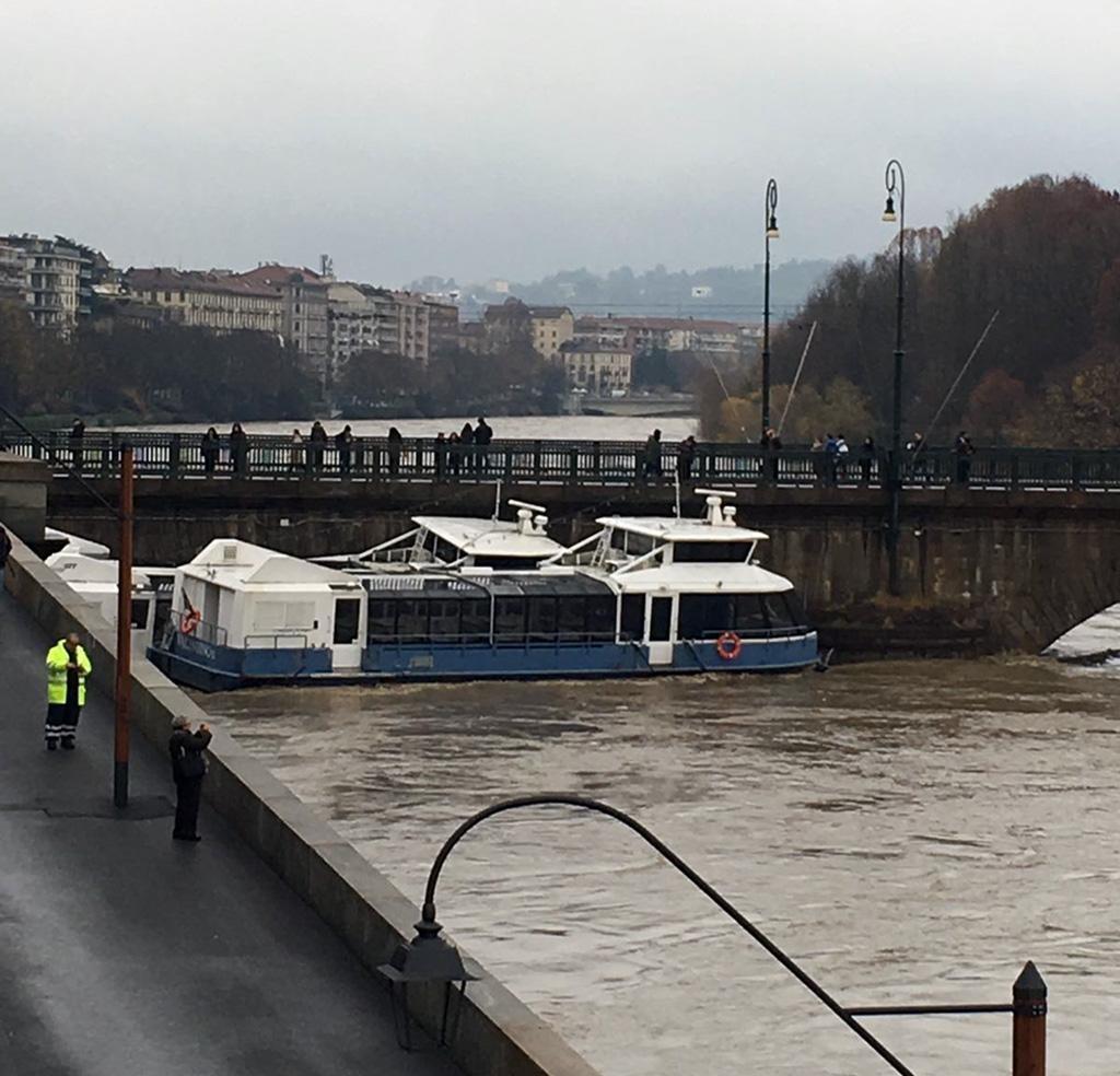Valentino e Valentina, i due battelli per la navigazione turistica sul Po, a Torino, sono stati trascinati via dalla forza del fiume, che ha rotto i loro ormeggi. Le due imbarcazioni si sono incastrate sotto le arcate del ponte della Gran Madre, nel centro del capoluogo. Il ponte è stato chiuso, 25 nvoembre 2016. ANSA/GALAVOTTI