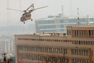 Un membro del comando sventola la bandiera dell'Isis dalla finestra dell'ospe