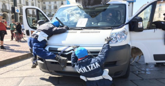 Poliziotti-fantocci appesi al furgone al corteo pro-cannabis